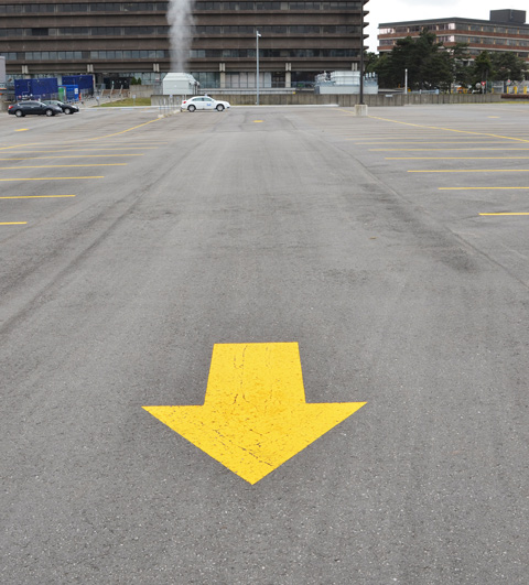large yellow arrow painted on the surface of a large parking lot, only a few cars