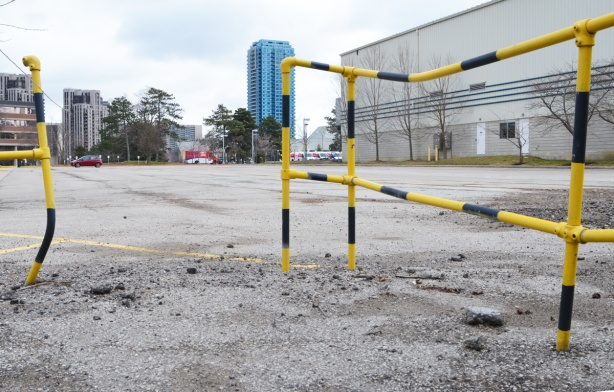 bent metal pipes as a railing, painted in yellow and black, empty parking lot beyond with a couple a buildings in the background