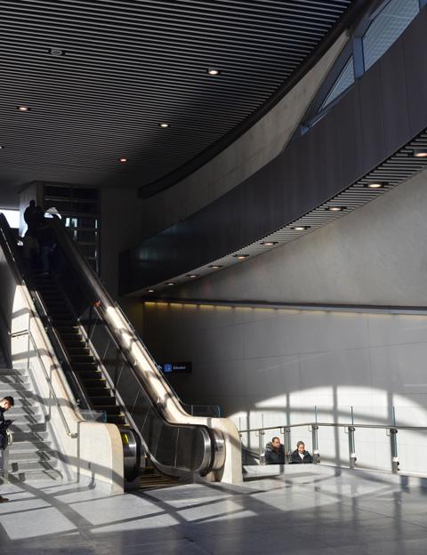 light shining through large windows into interior of York univeristy subway station, escalators, people coming up escalators,