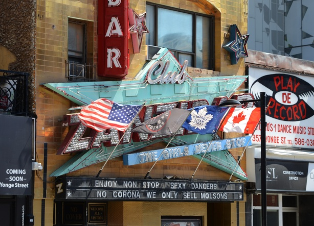 In front of the zanzibar club, sign, with flags and words, that say no corona here we only sell Molsons,