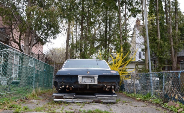 old blue car, Pontiac Parisienne, with its back bumper on the ground, parked off the street between two houses