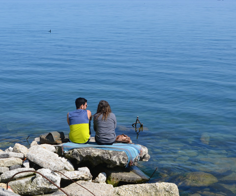 a couple sit on a rock by Lake Ontario