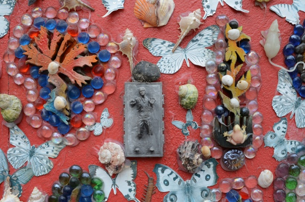 objects attached to a red wall, the exterior of a garage, plastic butterflies, beads, shells, and a small grey metal artwork that looks like a man emerging from a grey wall