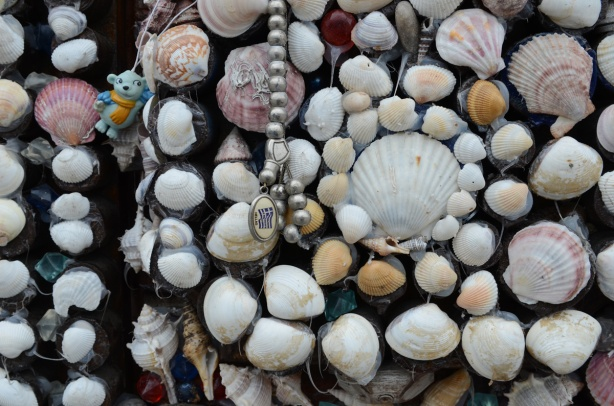 a collection of shells used in decorating the exterior surface of a garage, also a small blue toy bear and some silver beads with a picture of the Greek flag