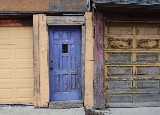 purple door in an alley, between two garage doors
