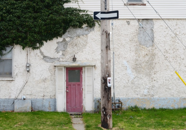 faded red, now pink, door on a white house, dirty and greyish stucco on the exterior, small bit of grass in front, one way sign on the utility pole in front of the house.