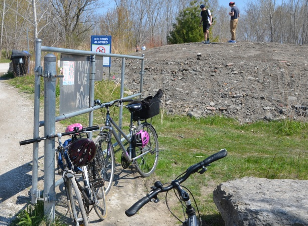 bikes parked against a fence with signs on it, with graffiti words that say flow like a river, in the background a mound of dirt with two young men standing on top of it.