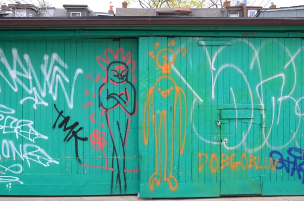 seafoam green colour garage door with graffiti drawings of people, dobgoblin,