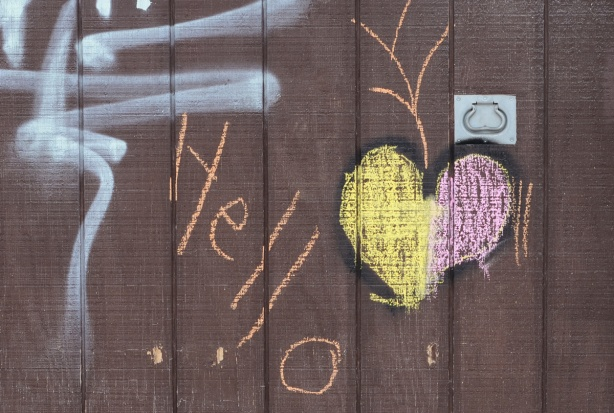 graffiti on a brown garage door, chalk heart in pink and yellow with orange word hello written beside it