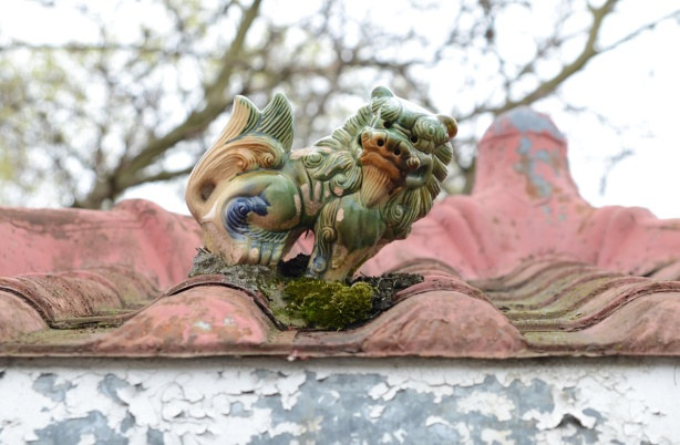 a ceramic ornament on top of a red tiled roof, animal, Chinese,