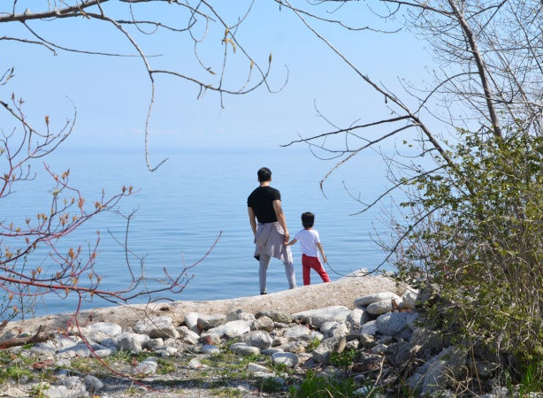 father and child standing on rocks at the shore of Lake Ontario