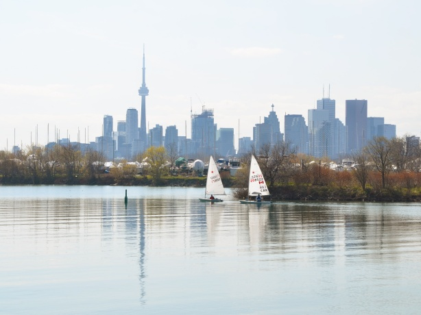 two sailboats exit the marina harbour and pass by the Toronto skyline (seen from the east)