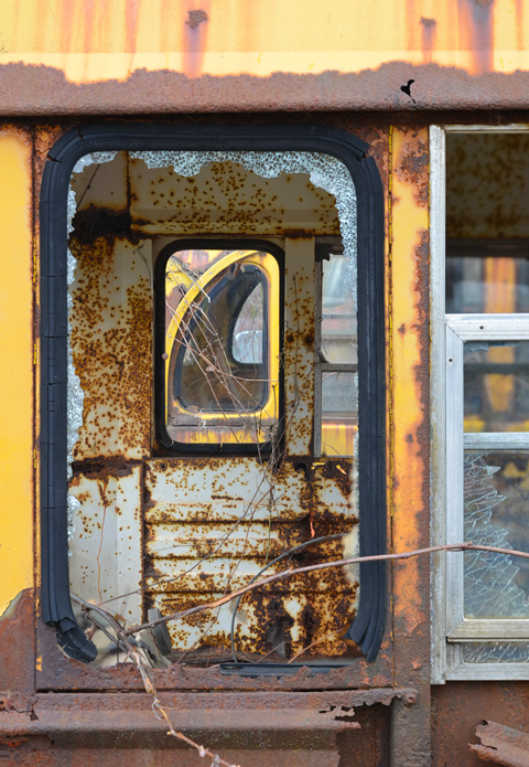 junked, old cars, McLeans Auto Wreckers, looking through broken side windows of a chool bus, back of bus, rusted, yellow,