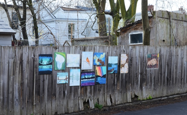 paintings on a wood fence, with backs of houses in the background
