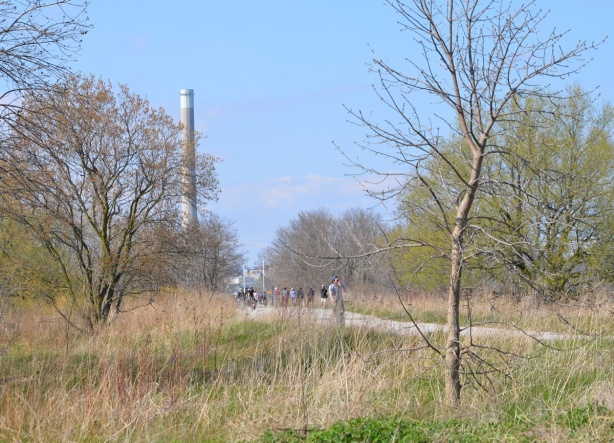 tall smokestack in the distance, a park in the foreground, with a bike path and cyclists running through the park, early spring