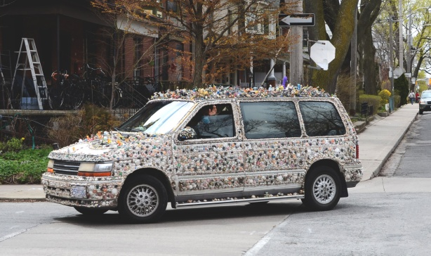 side of van covered with shells and small toys, driver is waving from partially lowered window