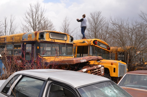 junked, old cars, McLeans Auto Wreckers, standing on top of a school bus, one of three buses rusting in field with other old vehicles