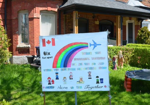 home made sign on the front yard of a house with a Canadian flag, a rainbow, and an airplane