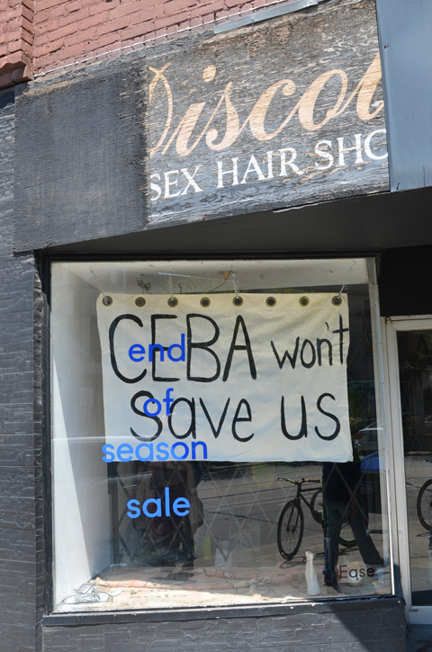 a sign in the window of a store that says CEBA won't save us, also blue letters advertising end of season sale