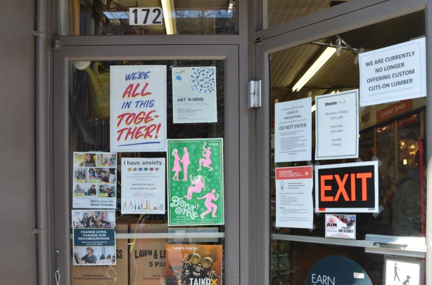 a large number of notices and posters on a glass door and window, including, we're all in this together,