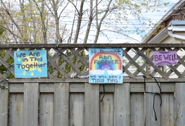 three small painted signs mounted on a wood fence, one says be well, another is a rainbow and the third says we're all in this together