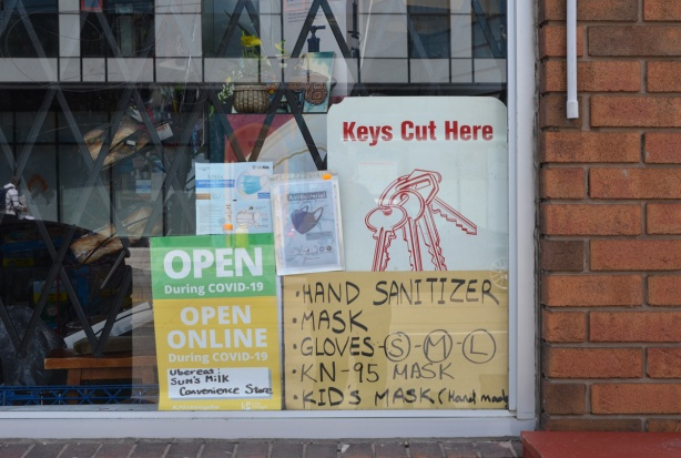 signs and posters in the window of a convenience store, Sun Milk, advertising hand sanitizer and kids face masks for sale, also keys cut,