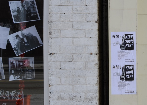keep your rent May 1 posters beside a gallery with photographs in the window