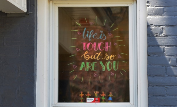 painted sign in the window of a house that says Life is tough but so are you