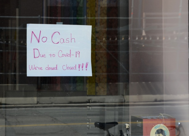 hand written sign in window of store, no cash, due to covid-19 we are closed