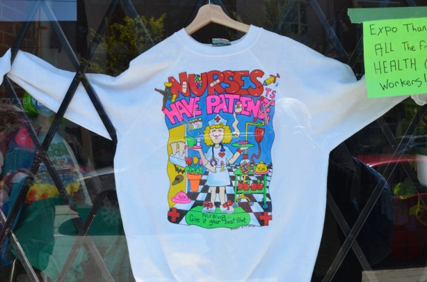 a white sweatshirt in the window of a store, that says Nurses have patience