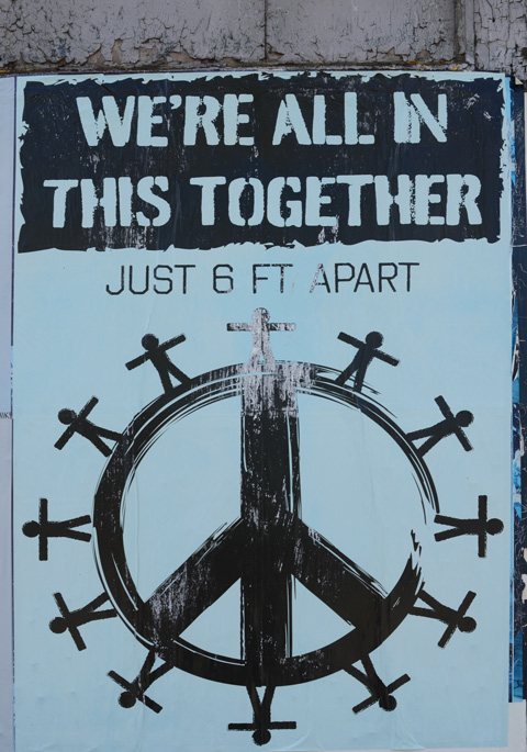 large poster for we're all in this together, peace symbol with stick figures standing around the outside of the circle