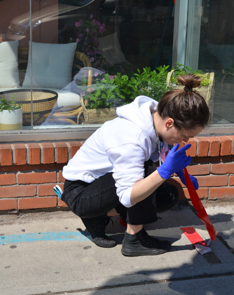 a young woman is marking a sidewalk with red tape, 6 feet apart for standing in line