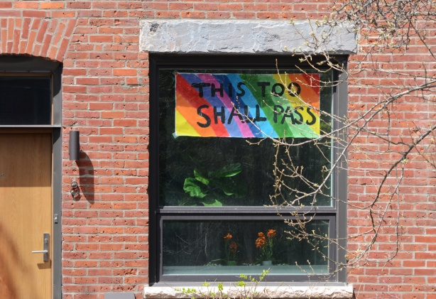 sign in window of house, rainbow with words this too shall pass