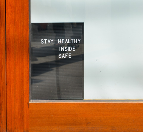small sign in the corner of a store window, blinds drawn, that says Stay Healthy Inside Safe