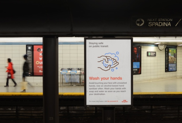 subway station platform, a couple of people walking, a sign reminding people to wash hands frequently and thoroughly because of covifd19