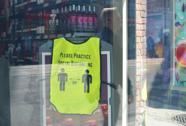 looking in the window of a wine store. A yellow vest is hanging by the counter, with words on vest that say please practice social distancing, two silhouette people 6 feet apart