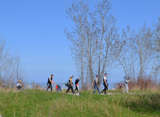 people walking on a trail in Tommy Thompson Park, early spring, trees just starting to form leaves