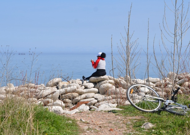 a woman looking at her phone, sitting on rocks by Lake Ontario, her bike is on the ground behind her
