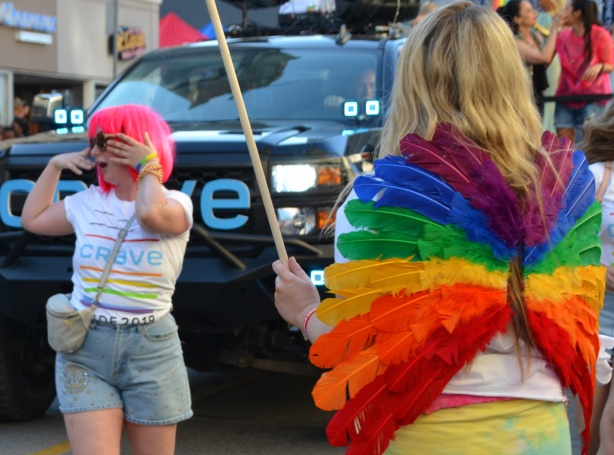 Pride parade, rainbow wings, dancing woman