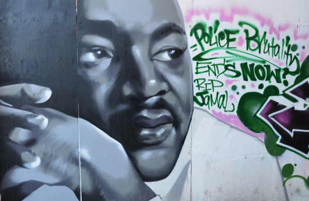 A portrait of Martin Luther King Jr. painted in a mural, along with words in green paint that say Police brutality ends R I P Jamal