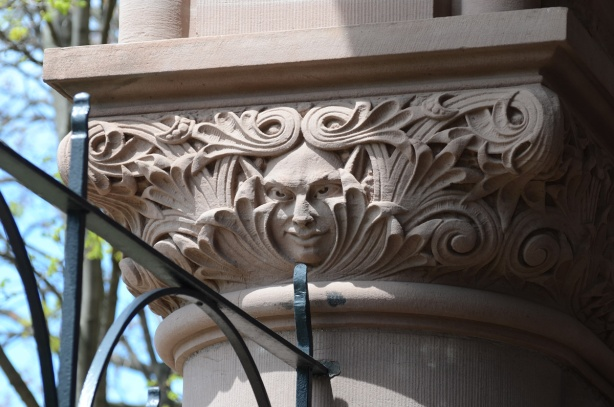 on a stone column, exterior of Queens Park, a face,