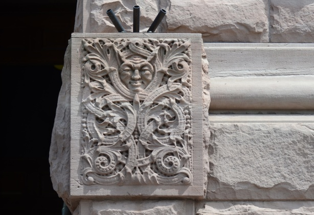 a man's face with what seems like horns from his head, a carving in stone