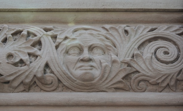 in a carved frieze on the exterior of parliament buildings, a face with blank eyes