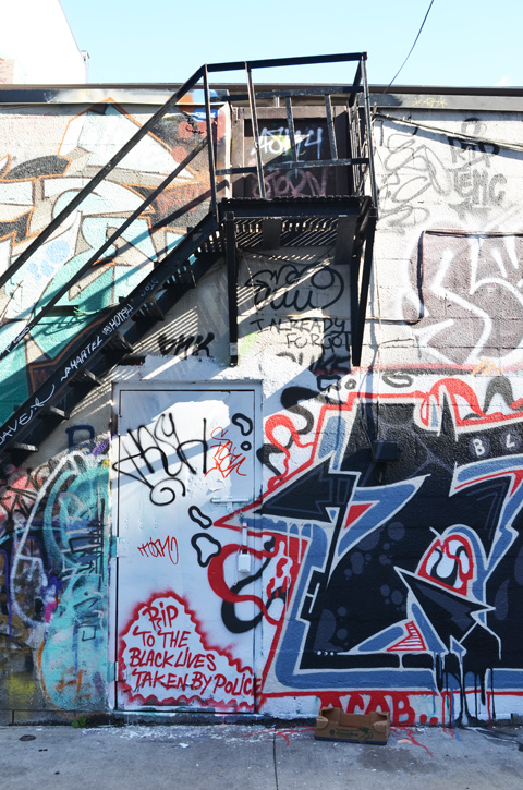 wall in Graffiti Alley, back of two storey building with exterior metal stairs, wall is covered with graffiti including words R I P to the black lives taken by police