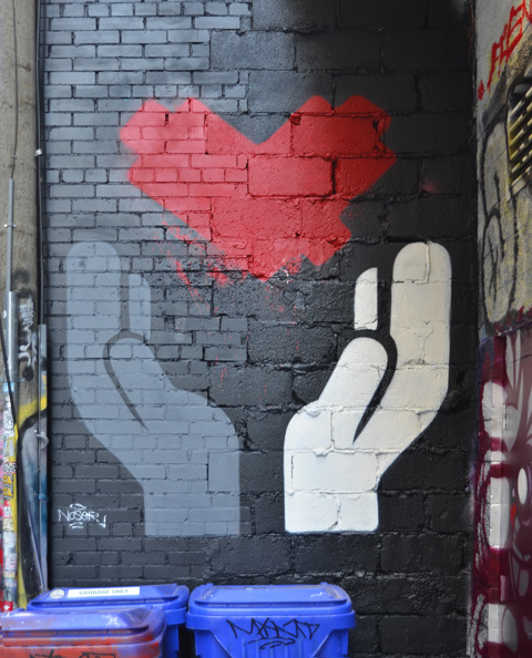 A mural in Graffiti Alley, A red lovebot heart with tow hands under it and appearing to hold it up, one hand is black and the other is white
