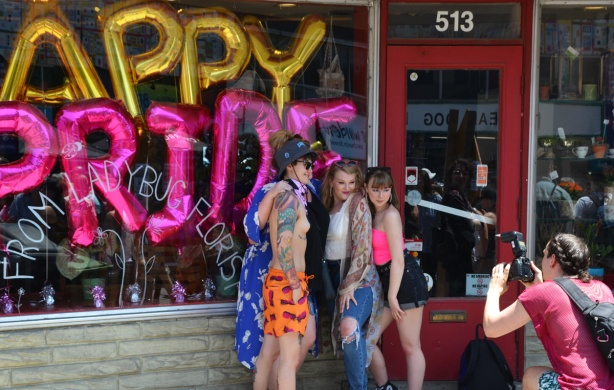 young people posing for pictures outside store with happy pride balloons in the window