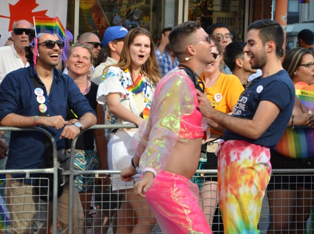 two people dancing, pride parade while spectators cheer