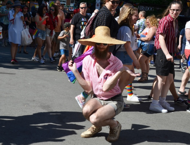 man in pink shirt and straw hat dances while squating while people passing by slow down to stare