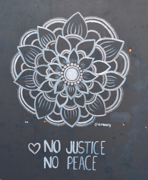 A circular design in light grey on black in a flower shape with words under that say no justice no peace