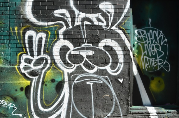 poser bunny mural in graffiti alley, giving peace sign, beside words that say black lives matter